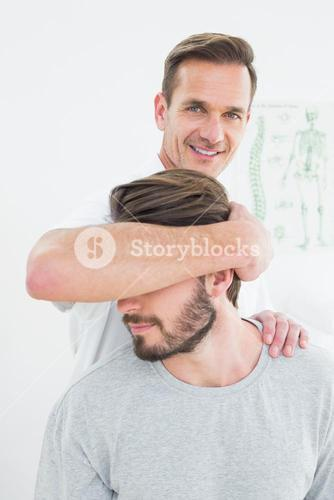Portrait of a male chiropractor doing neck adjustment