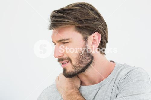 Closeup of a young man suffering from shoulder pain