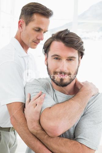Male physiotherapist examining a young man