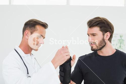 Male physiotherapist examining a mans wrist
