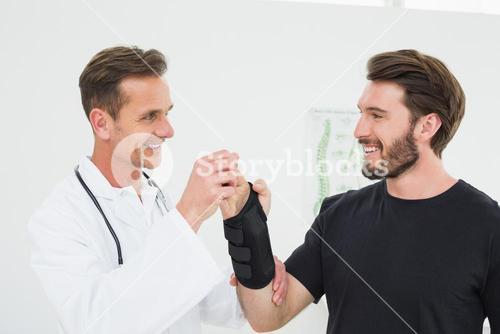 Male physiotherapist examining a young mans wrist