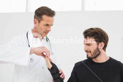 Male physiotherapist examining a young mans wrist in