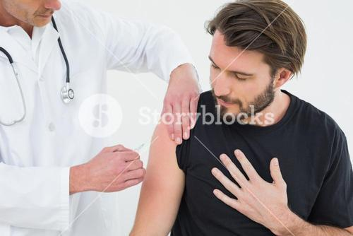 Male doctor injecting a young male patients arm