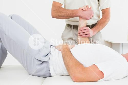 Physiotherapist examining a mans hand