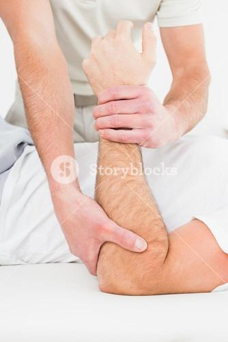 Mid section of a physiotherapist examining a mans hand