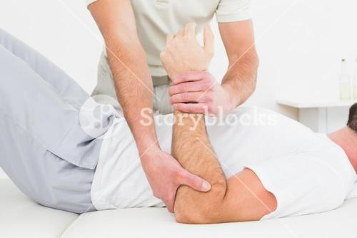 Mid section of physiotherapist examining a mans hand