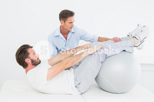 Physical therapist assisting young man do sit ups