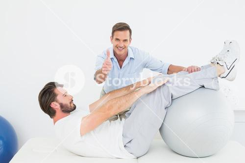 Therapist gestures thumbs up while assisting man do sit ups