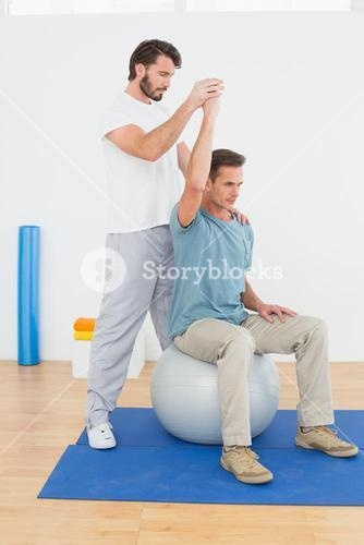 Man on yoga ball working with a physical therapist