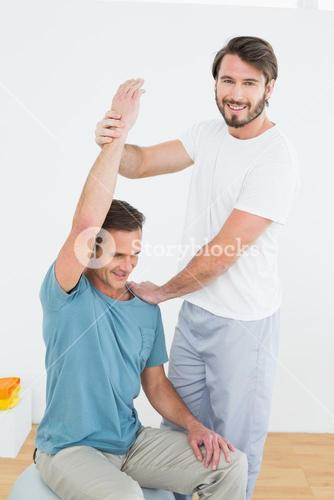 Physical therapist assisting man with stretching exercises