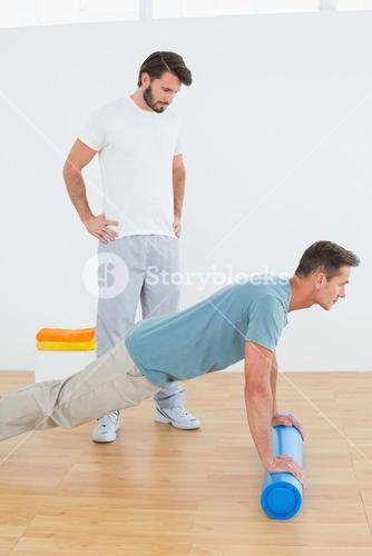 Physical therapist watching young man do push ups
