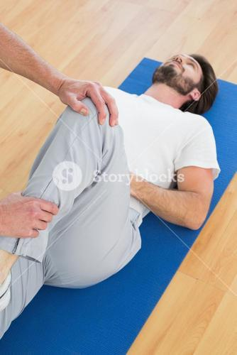 Physical therapist examining mans leg
