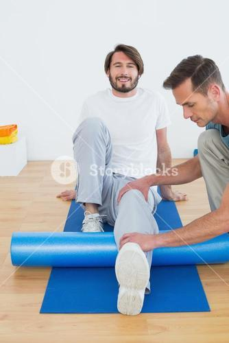 Physical therapist examining young mans leg