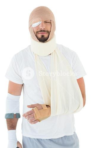 Young man with head tied up in bandage and broken hand