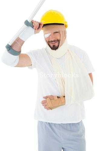 Portrait of a man in hard hat with broken hand and crutch