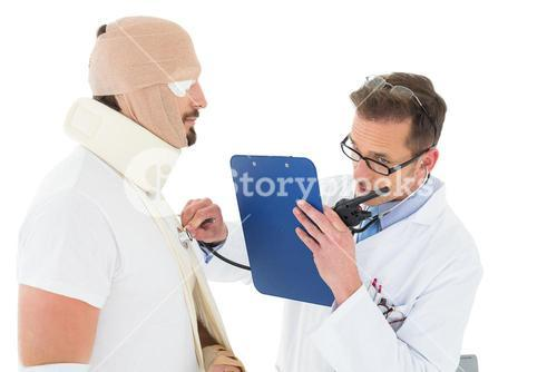 Doctor auscultating patient tied up in bandage with stethoscope