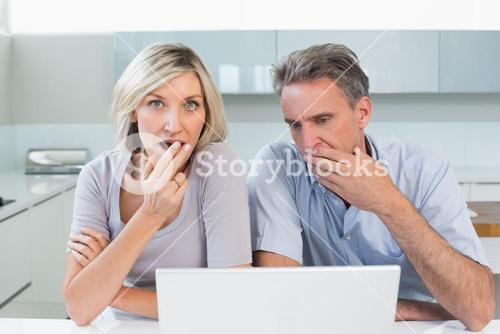 Shocked couple with laptop in kitchen