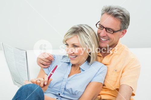 Happy couple doing the newspaper crossword puzzle at home