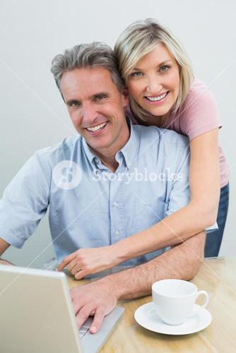 Content couple using laptop at home