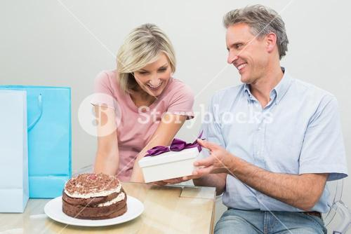 Man giving a happy woman a birthday gift beside cake