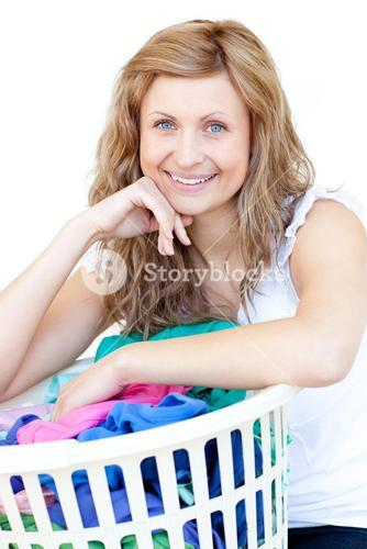 Happy woman doing laundry against a white background