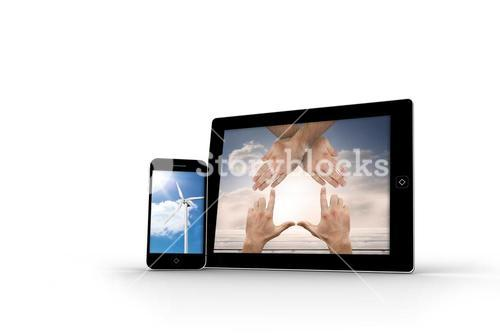 Hands and wind turbine on smartphone and tablet screens