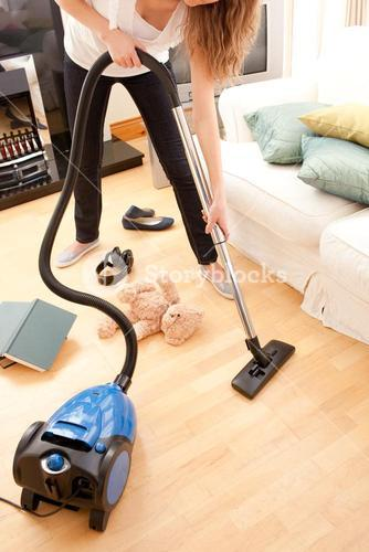 Young woman vacuuming the livingroom
