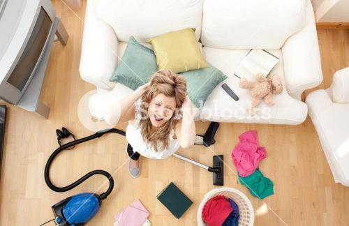 Stressed blond woman vacuuming the livingroom