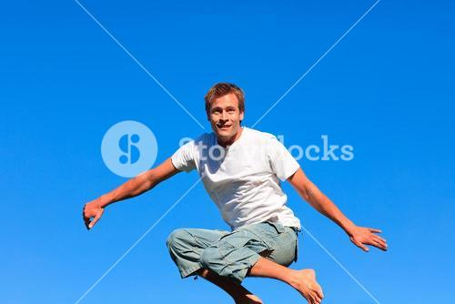 Selfassured man jumping against a blue background