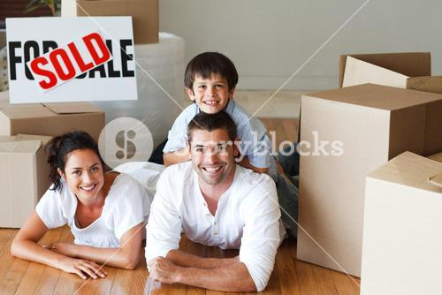 Happy parents and son lying on the floor after buying house