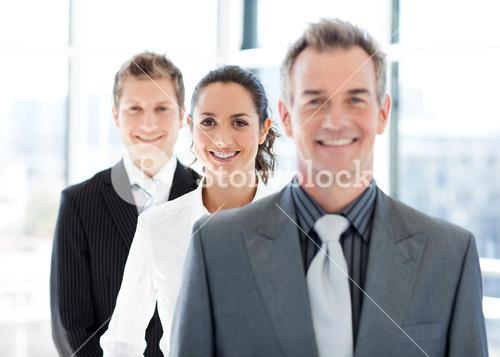 Smiling businesswoman in focus with her team