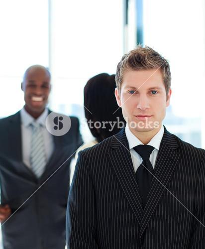 Serious businessman in front of his team