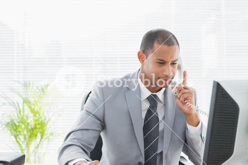 Businessman using computer and phone at office