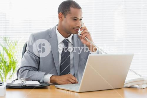 Businessman using laptop and phone at desk