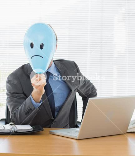Businessman with sad smiley faced balloon at office desk
