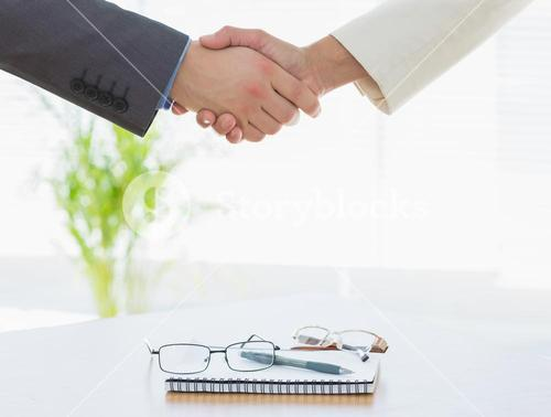 Shaking hands over eye glasses and diary after business meeting