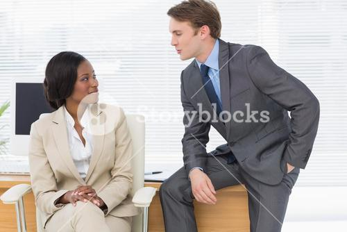 Colleagues conversing in office