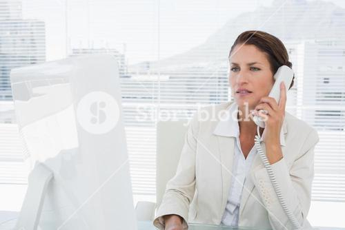 Businesswoman using computer and phone