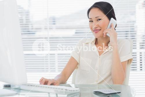 Businesswoman using cellphone and computer at desk