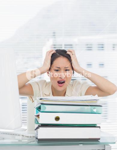 Angry businesswoman shouting with stack of folders at desk