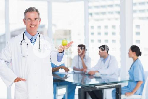 Doctor holding apple with group around table at hospital