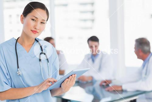 Surgeon using digital tablet with group around table in hospital