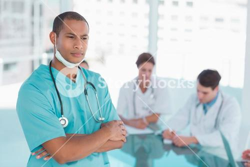 Surgeon standing with group around table in hospital