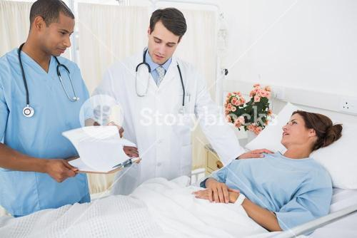 Doctors visiting female patient in hospital