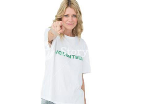 Portrait of a happy female volunteer pointing at you