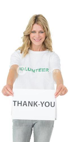 Smiling young female volunteer holding thank you paper