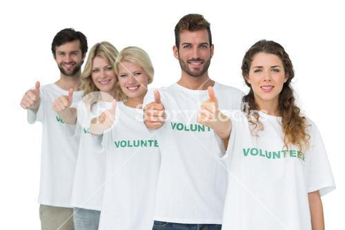 Group portrait of happy volunteers gesturing thumbs up