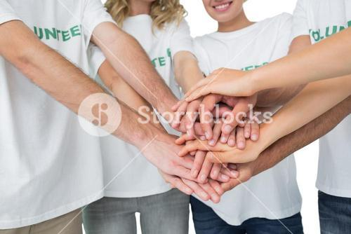 Mid section of volunteers with hands together