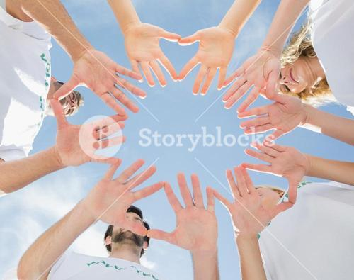 Volunteers with hands together against blue sky
