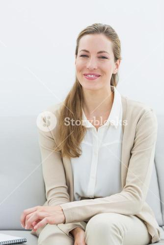Smiling psychologist sitting on sofa